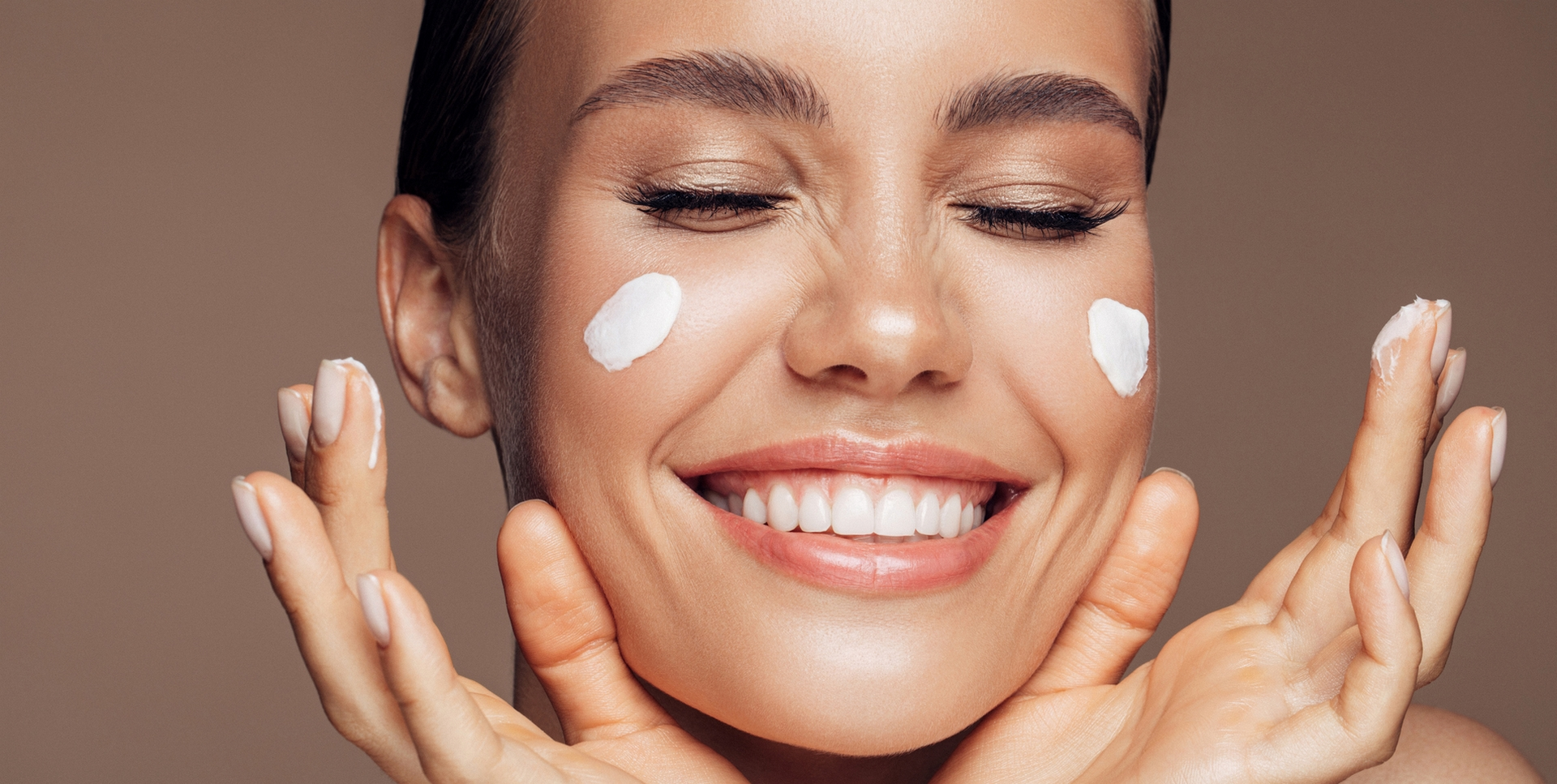 jeune femme souriante avec de la crème sur le visage